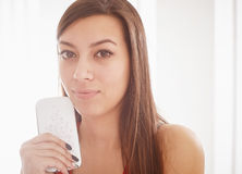 Young Woman Holding a Cellphone. Young pretty woman holding a mobile phone and looking away. Close up picture Stock Photos