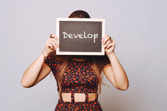 Young woman holding a chalkboard saying develop Stock Images