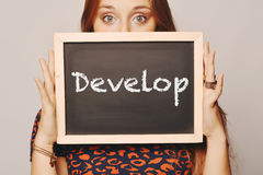 Young woman holding a chalkboard saying develop Stock Photo