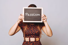 Young woman holding a chalkboard saying passion Royalty Free Stock Image