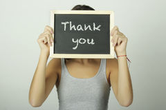 Young woman holding a chalkboard saying Thank you Stock Photo