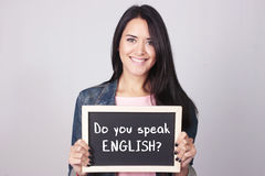 Young woman holding chalkboard that says Do You Speak English?. Young beautiful woman holding a chalkboard that says Do You Speak English Royalty Free Stock Images