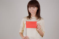 Young woman holding Chinese flag. Waist up of young Asian woman holding Chinese flag Royalty Free Stock Photos
