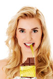 Young woman holding chocolate and eating measure tape Royalty Free Stock Photo