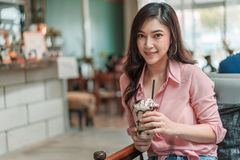 Woman holding chocolate frappe with whipped cream in the cafe. Young woman holding chocolate frappe with whipped cream in the cafe royalty free stock photos