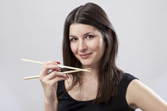 Young woman holding chopsticks. Young woman holding a pair of chopsticks Stock Photos