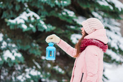 Young woman holding Christmas candlelight outdoors on beautiful winter snow day Royalty Free Stock Photography
