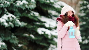Young woman holding Christmas candlelight outdoors on beautiful winter snow day stock video