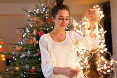 Young woman holding Christmas lights. Smiling royalty free stock photography