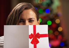 Young woman holding christmas postcard in front of face Stock Photo