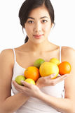 Young Woman Holding Citrus Fruit In Studio Stock Photo