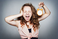 Young woman holding a clock Royalty Free Stock Photos