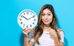 Young woman holding a clock. On a blue background Royalty Free Stock Photography