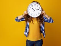 Young woman holding clock in front of face Royalty Free Stock Photography
