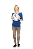 Young woman holding a clock. Stock Photo