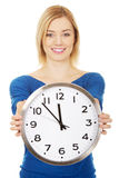 Young woman holding a clock. Royalty Free Stock Photo