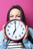 Young woman. Holding a clock on pink background stock photo