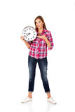 Young woman holding clock and pointing for it Royalty Free Stock Images