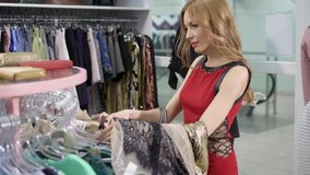A young woman is holding clothes on a hanger, a lady wants to update her wardrobe in the upcoming season. A young woman looks at fashionable clothes, which stock footage