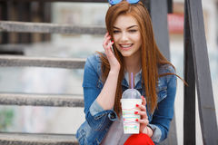 A young woman, holding a cocktail and making a phone call on a mobile phone Stock Image