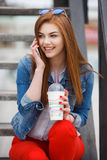 A young woman, holding a cocktail and making a phone call on a mobile phone Royalty Free Stock Images
