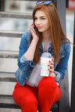 A young woman, holding a cocktail and making a phone call on a mobile phone Royalty Free Stock Photography