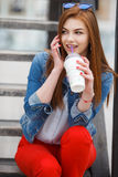 A young woman, holding a cocktail and making a phone call on a mobile phone Stock Photo
