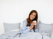 Young woman holding coffee cup in bed Stock Photos