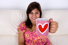 Young woman holding coffee cup with heart shape Stock Photo