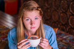 Young woman holding a coffee cup with her face printed on the foam Stock Photos