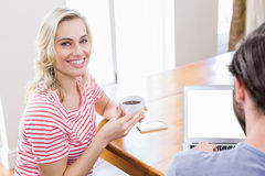 Young woman holding coffee mug while man using laptop Stock Images