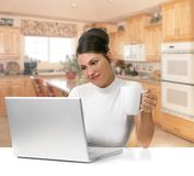 Young Woman Holding Coffee While Working on Her La. Beautiful Young Woman Holding Coffee While Working on Her Laptop Computer Royalty Free Stock Photography