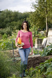 A young woman holding a colander full of vegetables royalty free stock photography