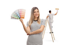Young woman holding a color swatch with a painter painting. Young women holding a color swatch with a painter painting climbed up a ladder isolated on white Royalty Free Stock Image