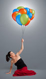 Young woman holding colorful balloons Stock Images