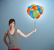 Young woman holding colorful balloons Stock Image