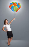 Young woman holding colorful balloons Stock Photo