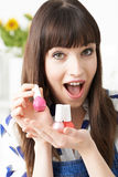 Young Woman Holding Colorful Bottles Of Nail Polish Royalty Free Stock Images