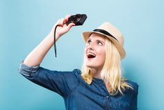 Young woman holding a compact camera. On a solid background Royalty Free Stock Images