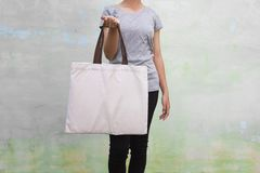young woman holding cotton bag on wall background. eco royalty free stock photo