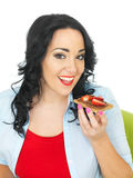 Young Woman Holding a Cracker with Chocolate Spread and Fresh Ripe Strawberries Stock Photo