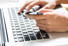 Young woman holding a credit card and typing. On-line shopping on the internet using a laptop Royalty Free Stock Photos