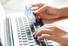 Young woman holding a credit card and typing. On-line shopping on the internet using a laptop Stock Photography