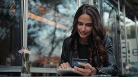 Young woman holding credit card and using laptop computer. Online shopping concept in modern cafe happy brunette girl
