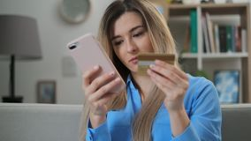 Young woman holding credit card and using smartphone. Online shopping concept, easy pay using digital mobile device. stock footage