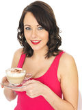 Young Woman Holding a Cup of Cappuccino Coffee Royalty Free Stock Photos