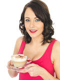 Young Woman Holding a Cup of Cappuccino Coffee Stock Photography