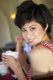 Young woman holding cup of coffee in cafe, looking over shoulder, smiling, close-up, rear view, portrait, focus on foreground Royalty Free Stock Image