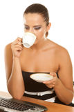 Young woman holding a cup of coffee at her workplace Stock Photos