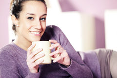 Young woman holding a cup of coffee i Stock Images